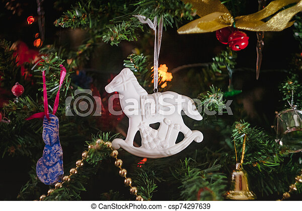 Christmas toys in the form of a white ceramic antique rocking horse with gifts on a decorated Christmas tree. Close-up. - csp74297639
