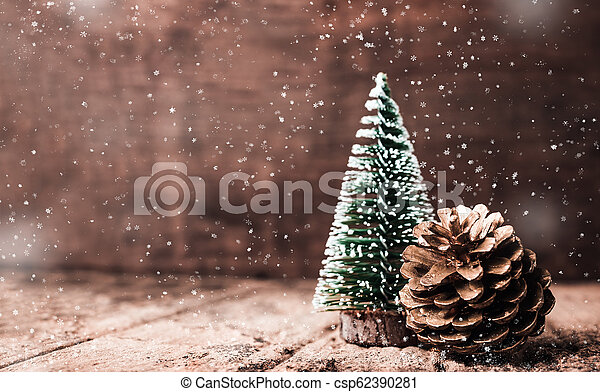 Christmas tree and gold pine cone and snow falling on grunge wood table and dark brown wooden wall. Winter Merry Christmas holiday greeting card. - csp62390281