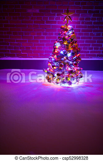 Christmas Tree With Festive Lights In Snow Outdoors Purple Brick Wall Background