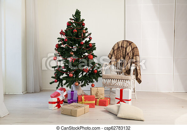 Christmas tree with presents in the room with a winter decoration for the new year - csp62783132