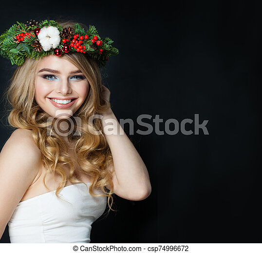 Christmas woman smiling on black background - csp74996672