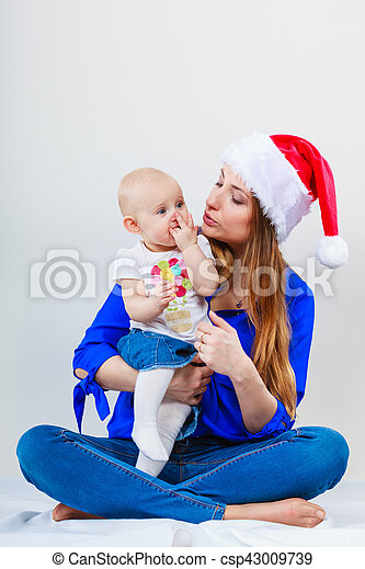 1237b3ea381b4 Family celebration concept. christmas woman with cute baby. beautiful lady  has red santa claus cap.