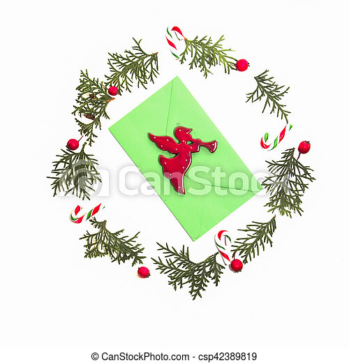 Christmas wreath made of thuja twigs, red wild rose fruits with green envelop and Xmas decoration cane in the middle. White background. Top view, flat lay. - csp42389819