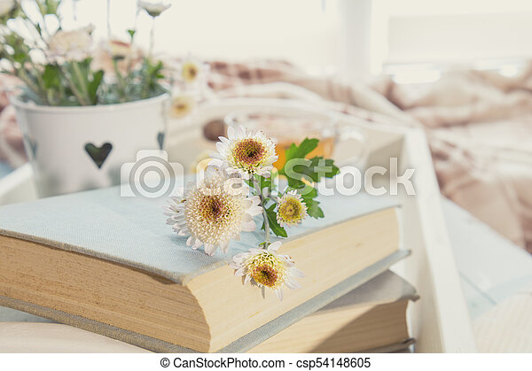 Chrysanthemum flowers lay on the book which is laying on the table. Cozy home concept - csp54148605