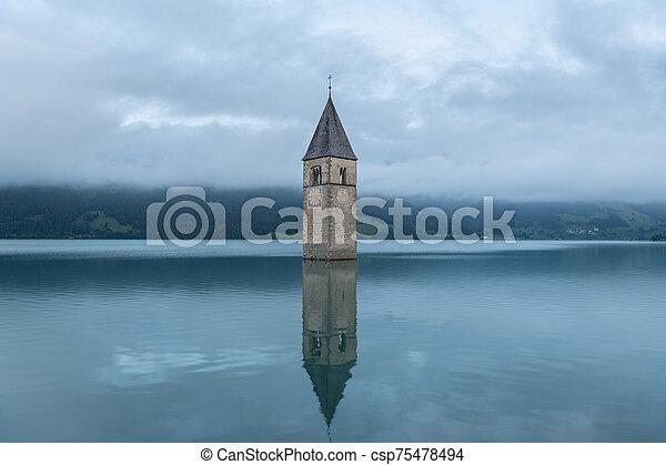 Church tower of Altgraun, Reschensee on a cloudy morning in summer - csp75478494