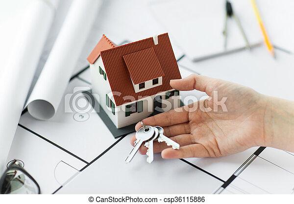 Cerrar de la mano con las llaves de la casa y los planos - csp36115886