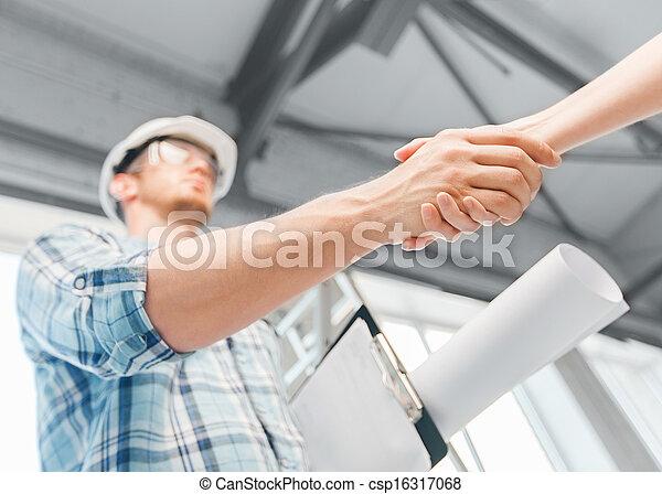 Constructor con anteproyecto estrechando la mano del socio - csp16317068