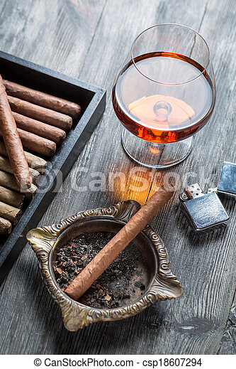 Cigar in ashtray, lighter and cognac - csp18607294