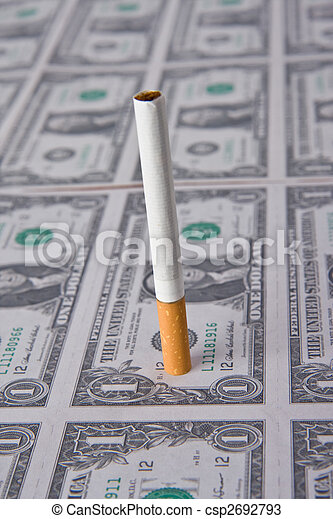 cigarette laying on money - csp2692793