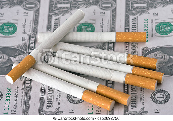 cigarettes laying on money - csp2692756