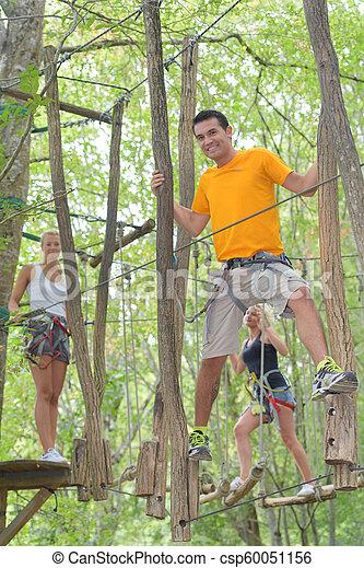 Hombre balanceándose sobre los árboles - csp60051156