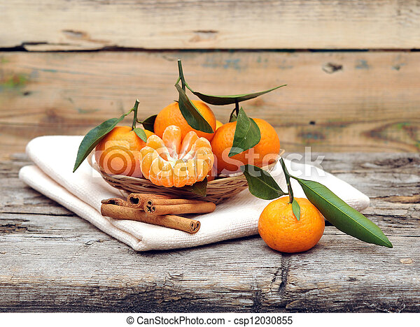 Cinnamon and tangerines with leaves on wooden table - csp12030855