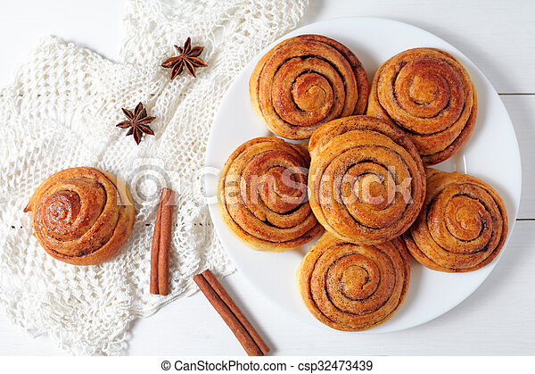 Cinnamon bun rolls christmas sweet dessert on white vintage table. Traditional swedish kanelbullar baked pastry. - csp32473439
