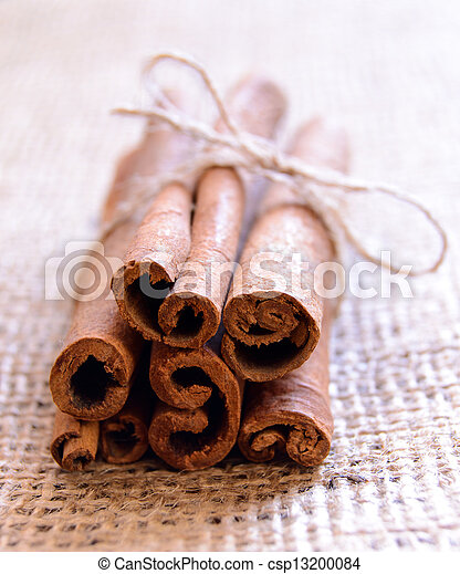 Cinnamon Sticks on Burlap Background - csp13200084