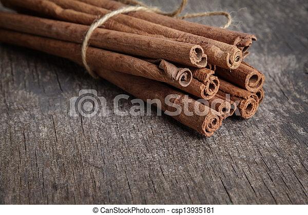 cinnamon sticks on old wooden table - csp13935181