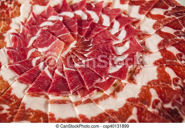 Circular decorative arrangement of iberian cured ham on plate - csp40131899