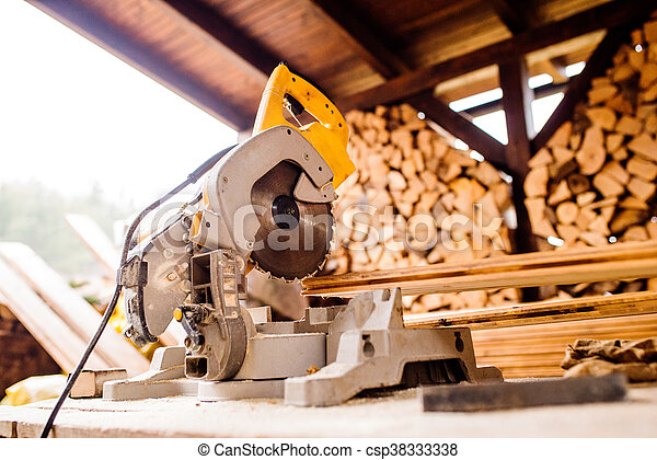 Circular saw laid on table, stack of wood behind it - csp38333338