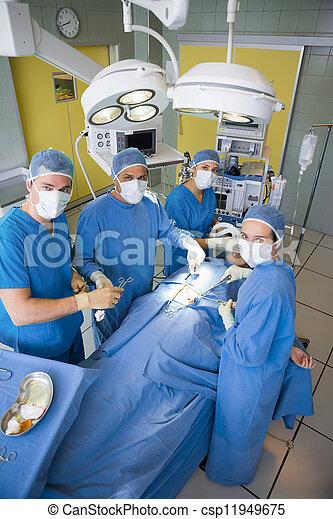 Equipo de cirugía mirando cámara durante la operación - csp11949675