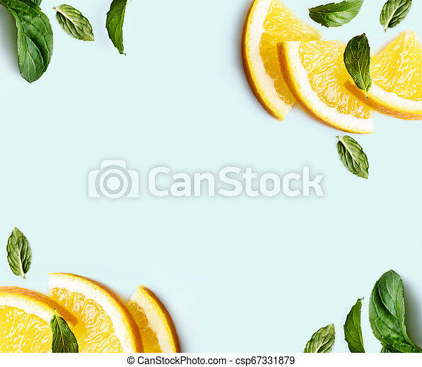 Citrus slices and mint herbs frame on retro mint pastel background with copyspace from above. Top view of lemon and orange refreshment. - csp67331879