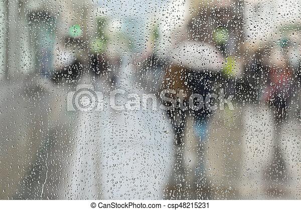 Antecedentes abstractos de dos jóvenes bajo el paraguas, caminan por la carretera en la ciudad bajo la lluvia. Las gotas de agua sobre el vidrio. Movimiento intencional borroso. Concepto de estaciones, ciudad moderna. - csp48215231