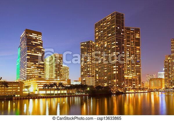 Ciudad de Miami Florida, horizonte nocturno. Un paisaje de edificios residenciales y de negocios iluminados por luces brillantes después del atardecer - csp13633865