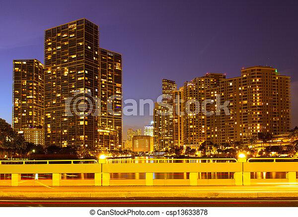 Ciudad de Miami Florida, horizonte nocturno. Un paisaje de edificios residenciales y de negocios iluminados por luces brillantes después del atardecer - csp13633878