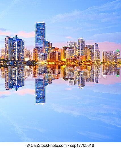 Ciudad de Miami Florida, horizonte nocturno. El paisaje urbano de edificios residenciales y de negocios iluminados al atardecer con reflexión - csp17705618