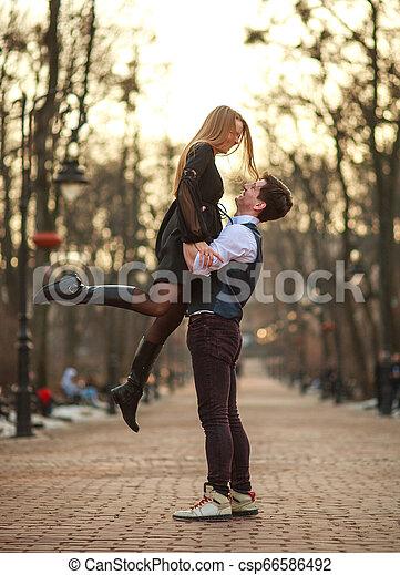 Una pareja joven y elegante enamorada con estilo clásico bailando apasionadamente en el parque - csp66586492