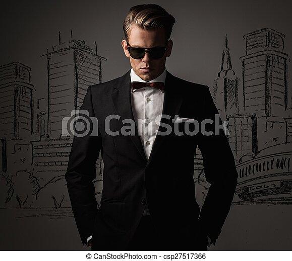 Un hombre vestido de negro contra un dibujo del panorama de la ciudad - csp27517366