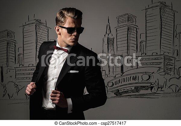Un hombre vestido de negro contra un dibujo del panorama de la ciudad - csp27517417