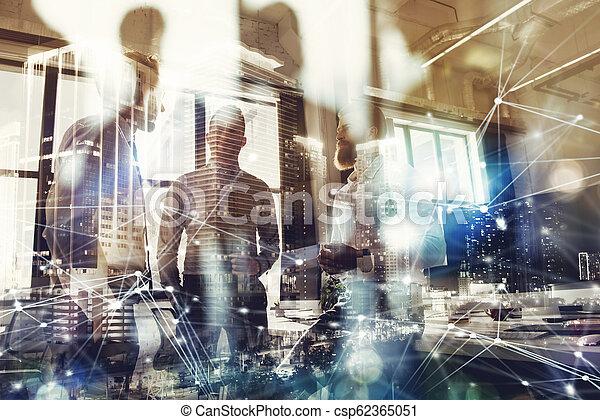 La gente de negocios trabaja juntas en la oficina. Concepto el trabajo en equipo y la sociedad. Doble exposición con la ciudad moderna y los efectos de la luz - csp62365051