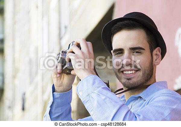 Una cámara de turismo vintage tomando fotos en la ciudad - csp48128684