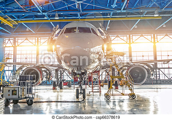 Civil airplane jet on maintenance of engine and fuselage check repair in airport hangar. Bright light at the gate - csp66378619