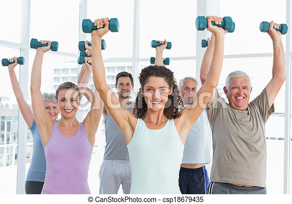 Class exercising with dumbbells in gym - csp18679435