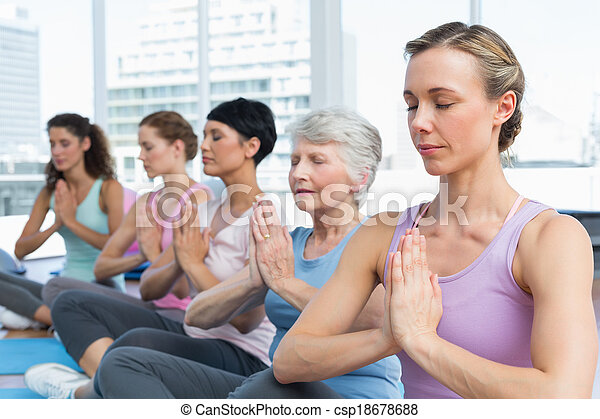 Class sitting with joined hands in a row at yoga class - csp18678688