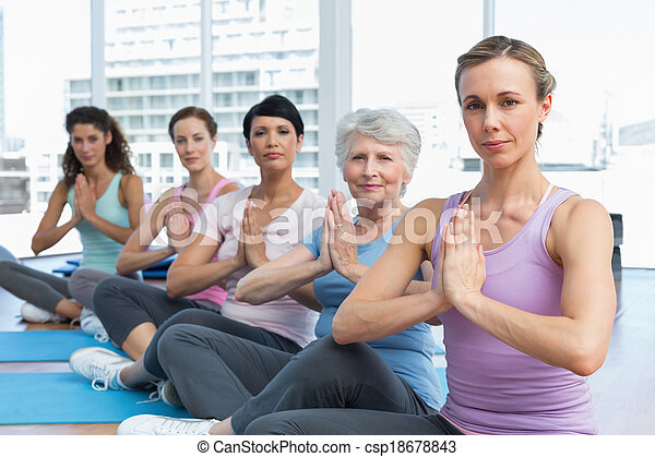 Class sitting with joined hands in a row at yoga class - csp18678843