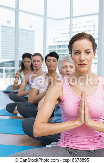 Class sitting with joined hands in a row at yoga class - csp18678895