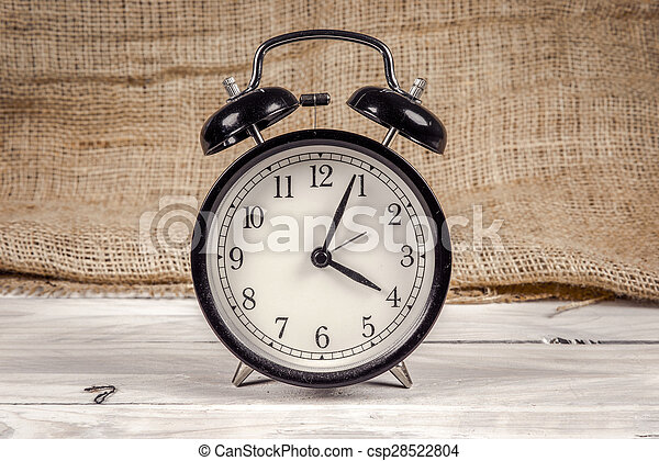 Classic alarm clock on a wooden table - csp28522804