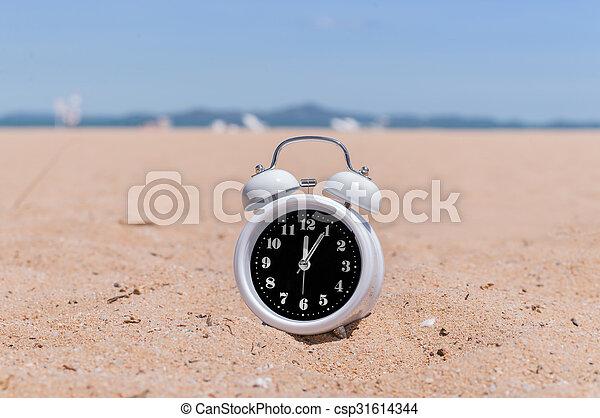 Classic analog clocks in sand on the beach - csp31614344