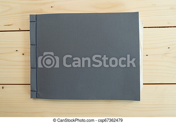 classic black notebook on the wood table. - csp67362479