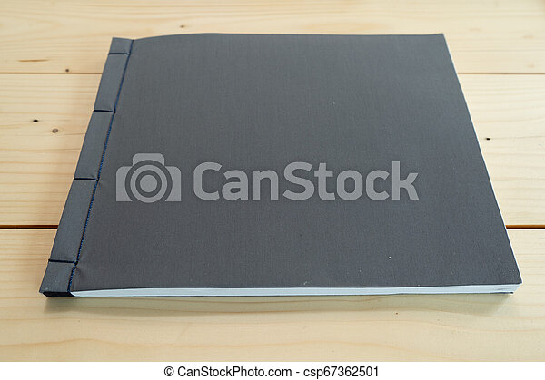 classic black notebook on the wood table. - csp67362501