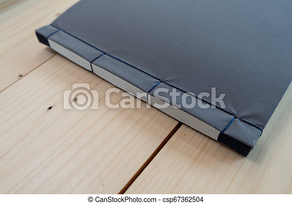 classic black notebook on the wood table. - csp67362504