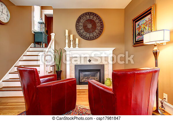 Classic designed family room with comfortable red chairs, light tones fireplace, hardwood floor and beige walls - csp17981847