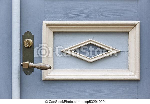 Classic doorknob on a vintage blue wooden door. Decoration - csp53291920