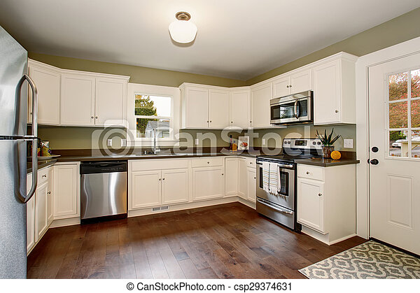 Classic kitchen with green interior paint, and white cabinets. - csp29374631