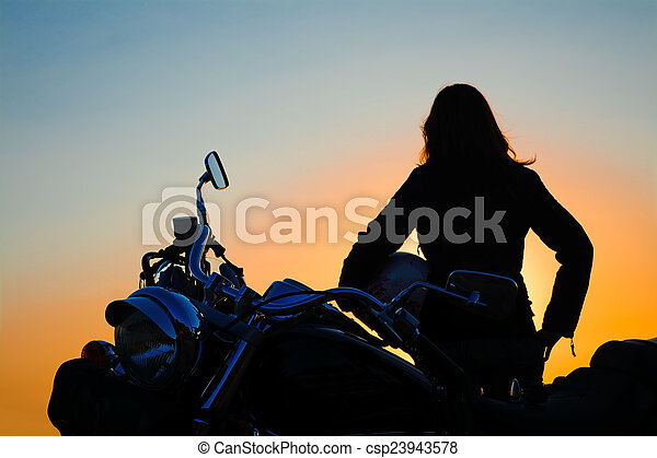 classic motorcycle and girl silhouette at sunset - csp23943578