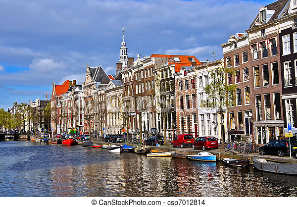 Classical Amsterdam view. Boat floats on the channel on the background of Dutch houses. Urban scene. - csp7012814