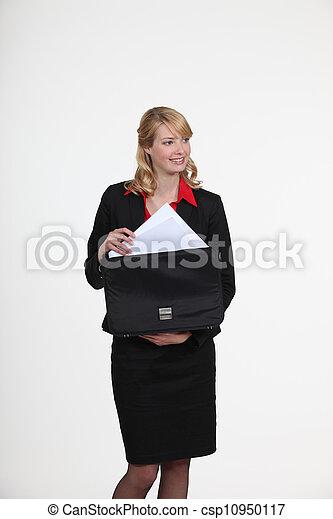 classy blonde businesswoman putting documents in briefcase - csp10950117