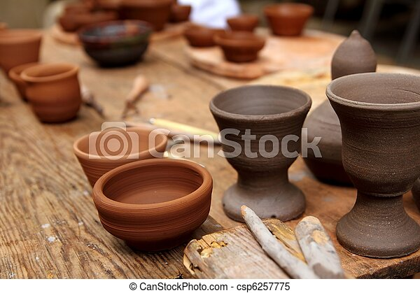 clay pottery potter handcrafts on vintage table - csp6257775