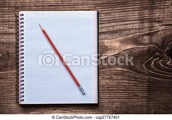 Clean squared copybook with pencil on pine brown wooden board ed - csp27767401